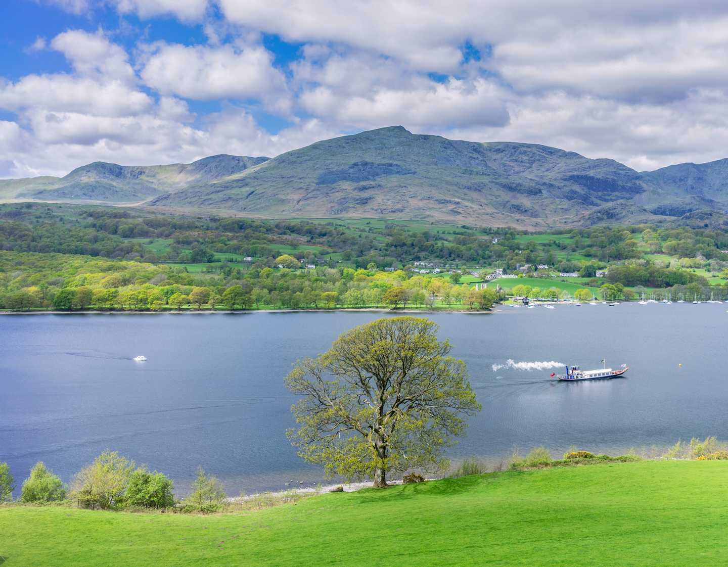 A boat on Coniston Water with the mountains in the background