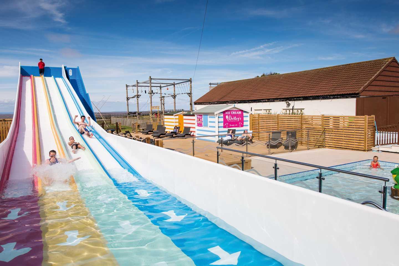 Guests sliding down the multi-lane pool slide