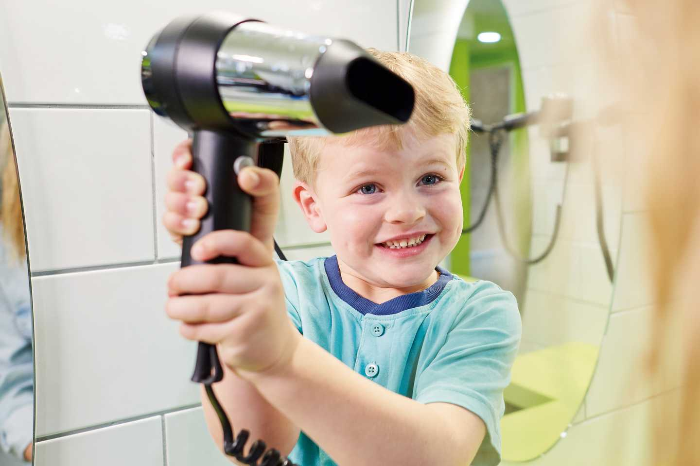 A young boy holding a hairdryer
