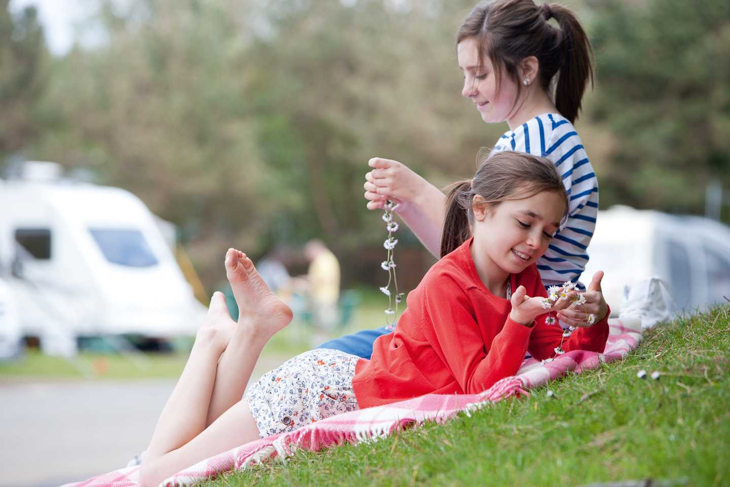 A child and mother making daisy chains in the touring area