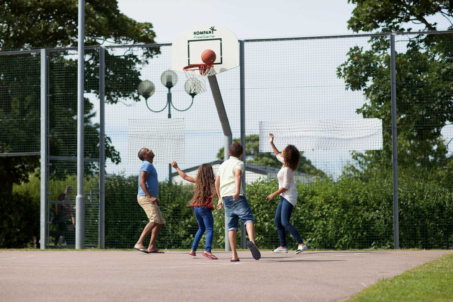 Family enjoying basketball on our all-weather multi-sports court