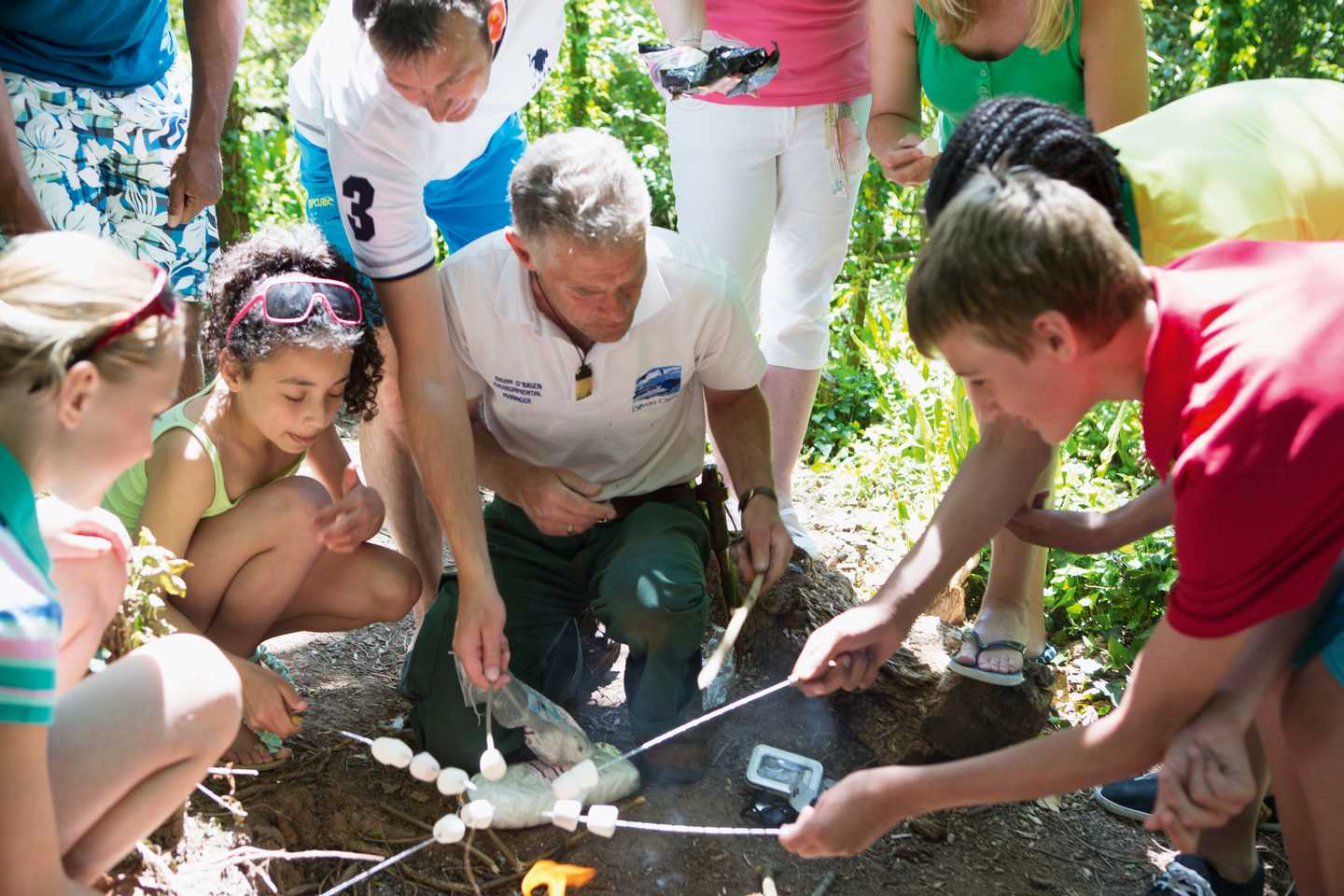 Guests cooking marshmellows round a lit fire with a Ranger, in our Nature Rockz bushcraft activity