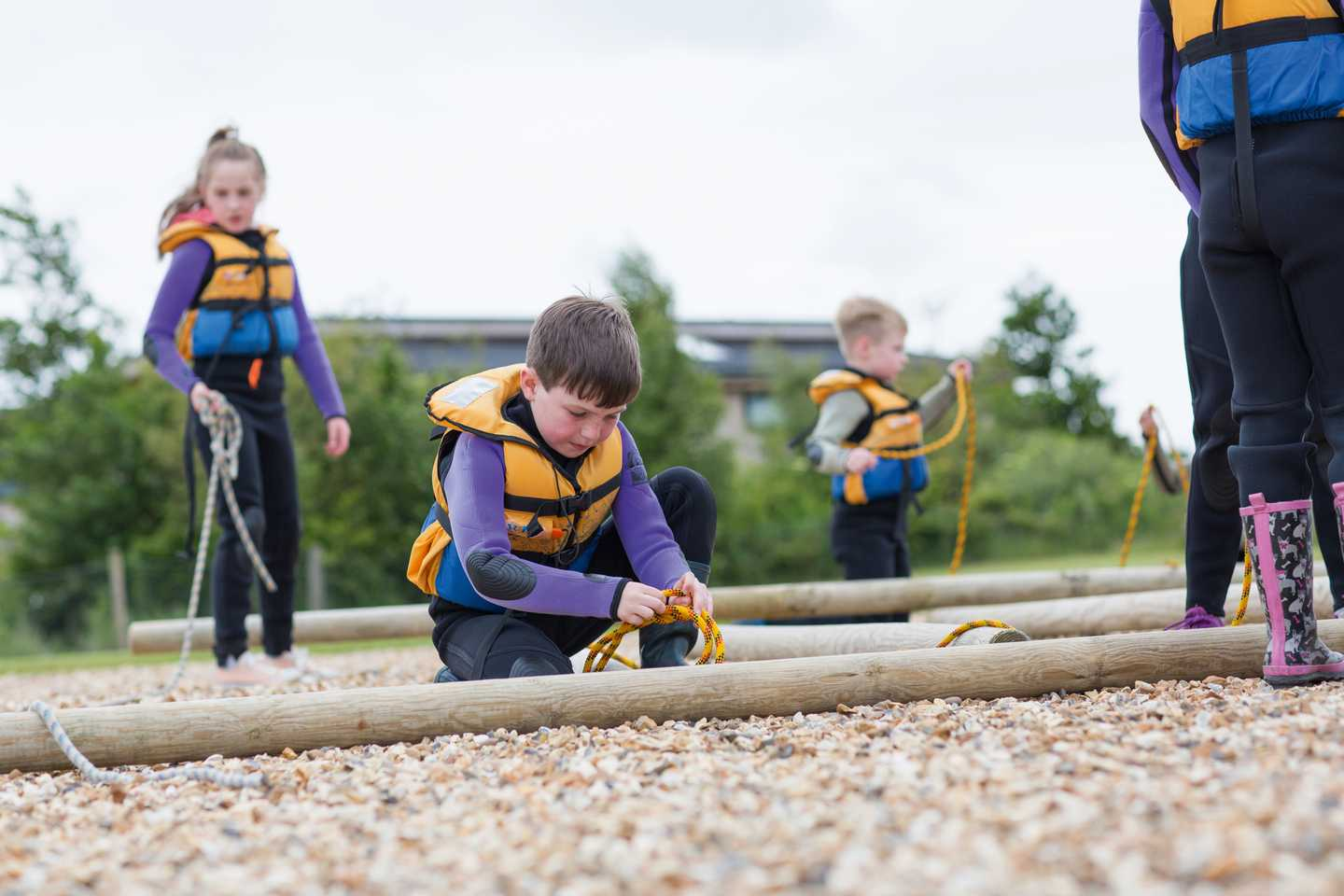 Children learning how to build a raft on the beach