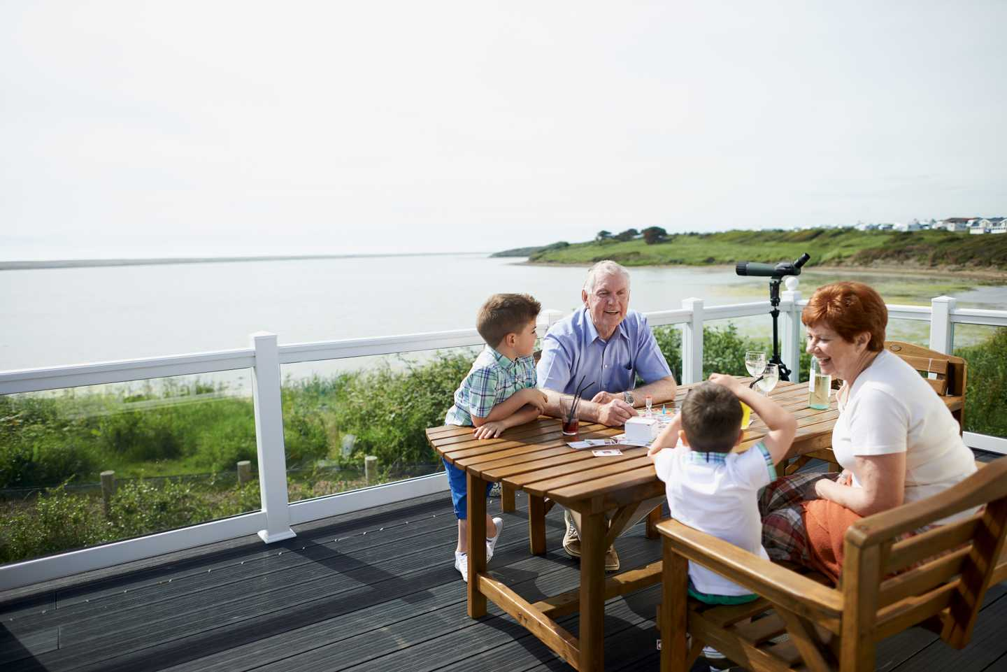 Family enjoying the sea view and playing a game, at the table on the veranda of their caravan