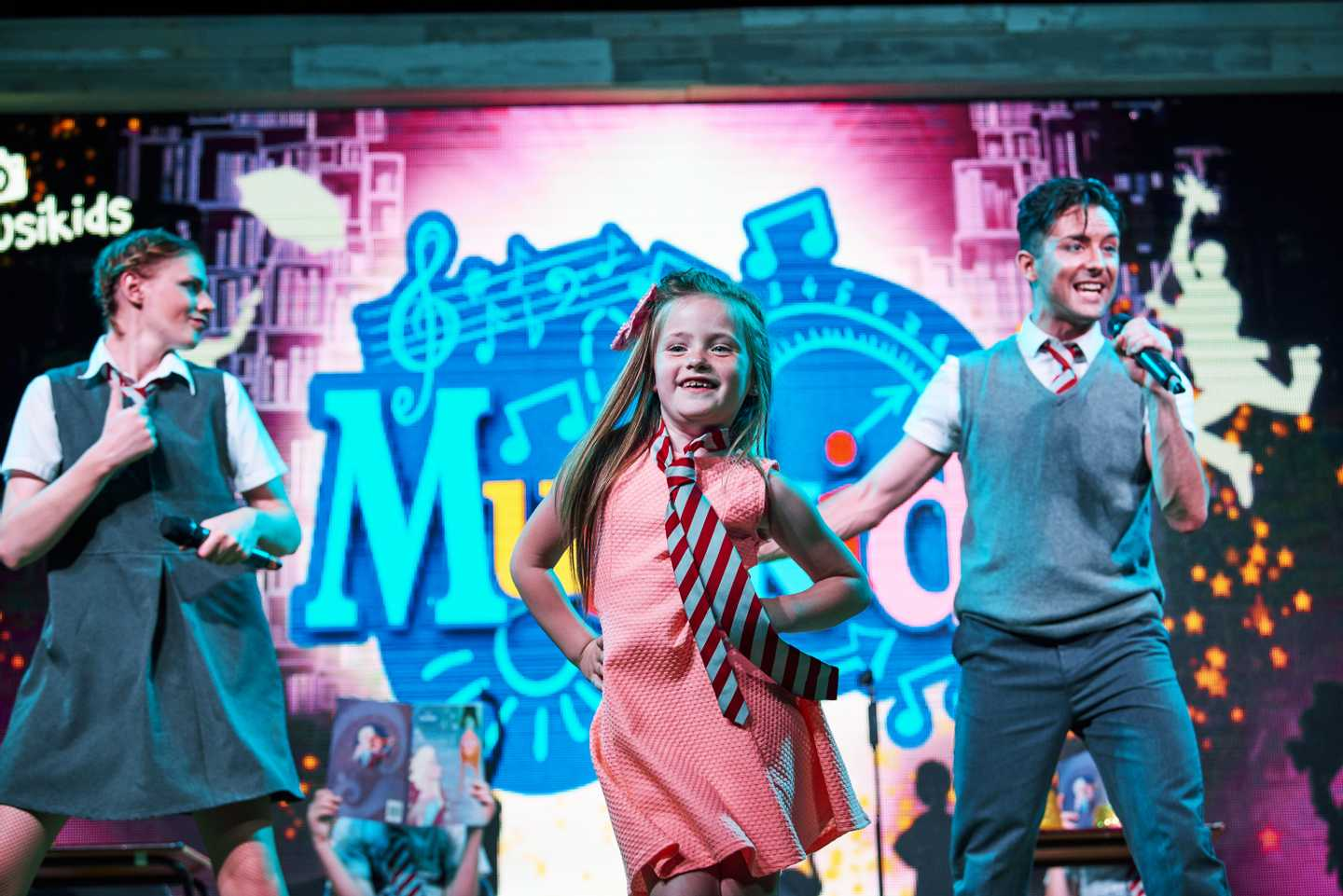 A girl and two adults performing onstage