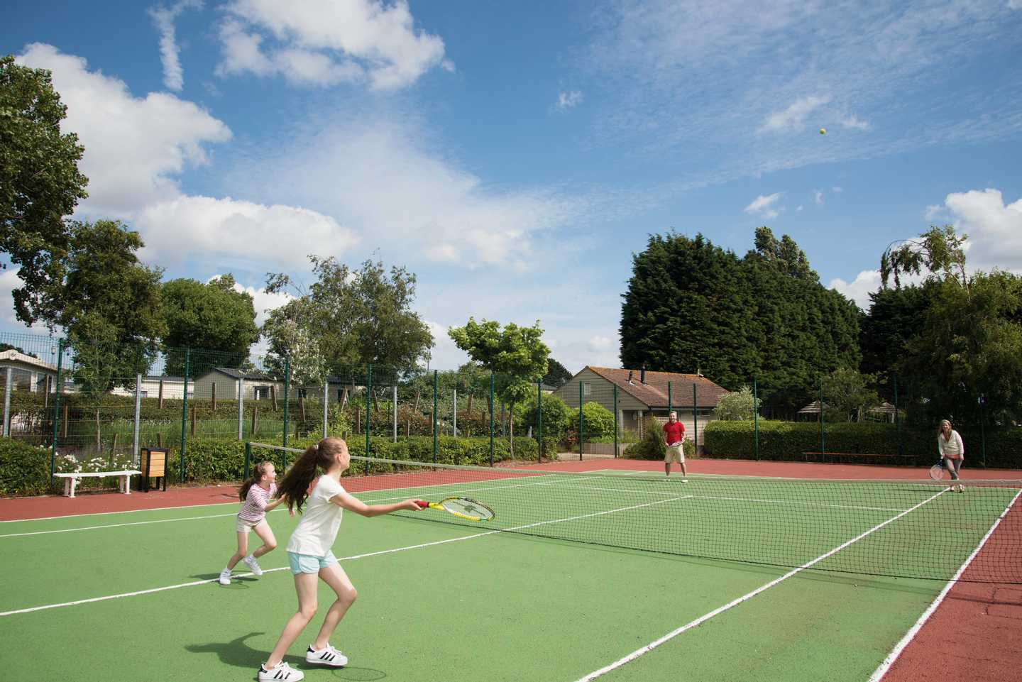 Family playing tennis at the tennis courts