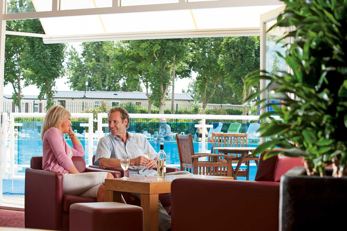 Guests enjoying a drink inside the Mash and Barrel overlooking the outdoor pool