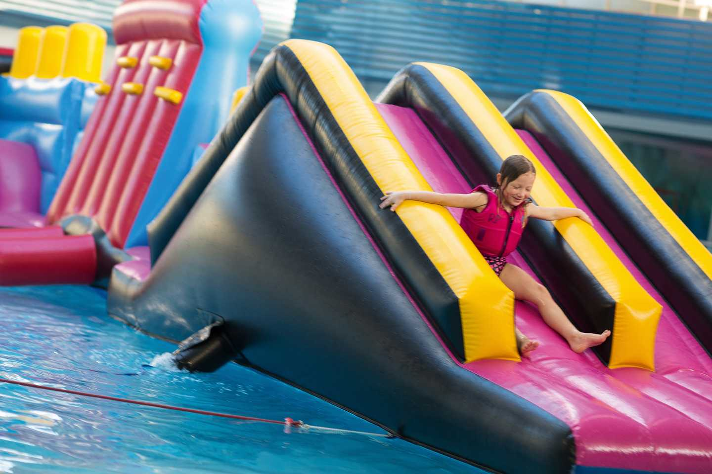 Child sliding down the inflatable slide, at Aqua Inflatable