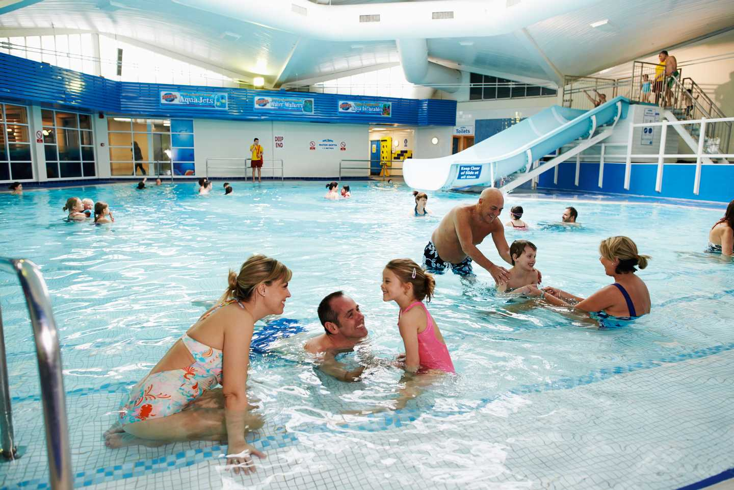 Guests splashing around in the heated indoor pool with slide
