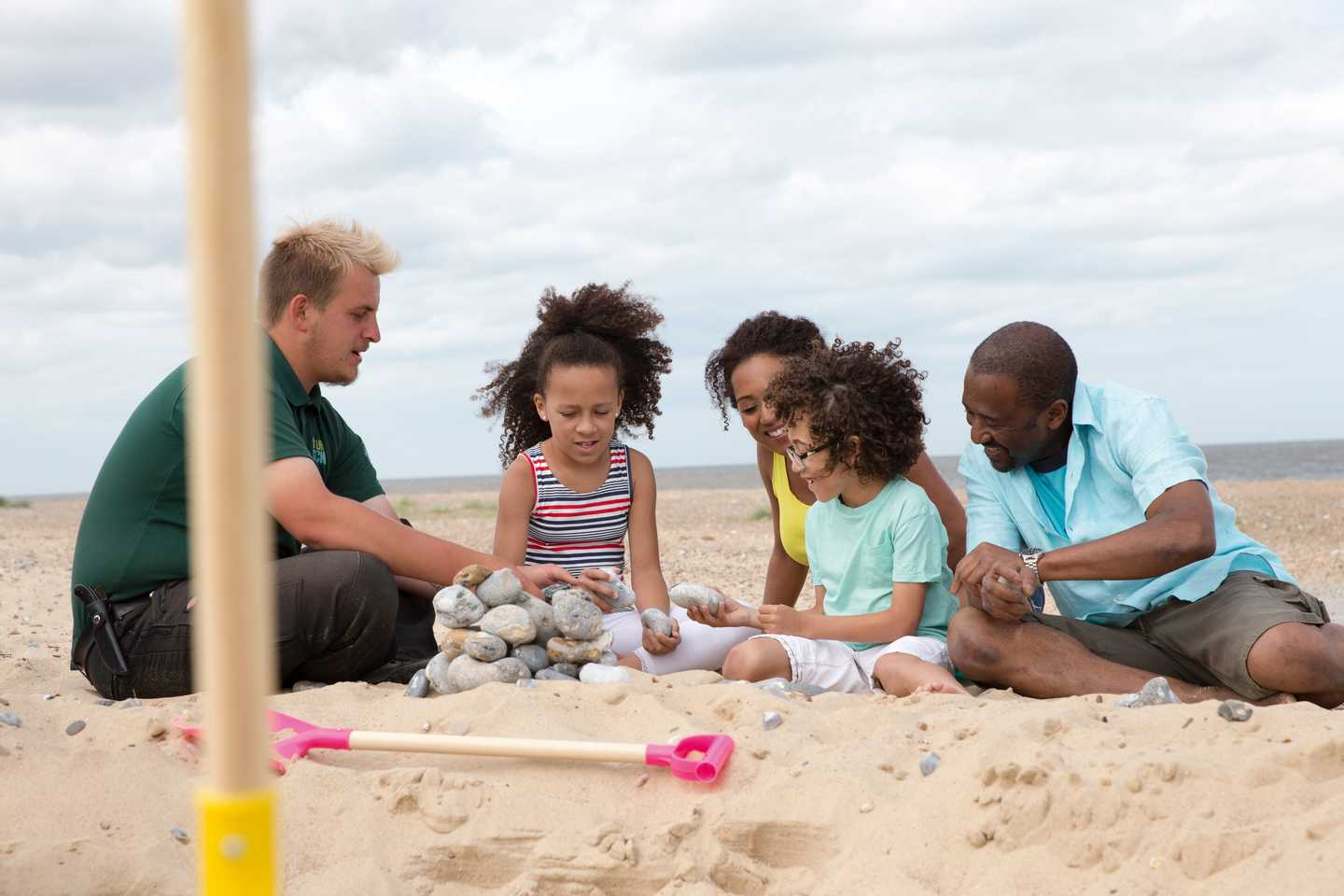 Guests on the beach with a Ranger building a tower with pebbles