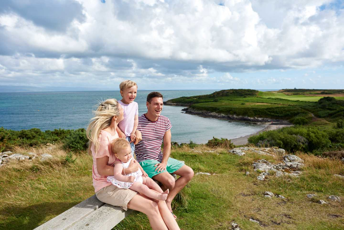 Family sitting on a bench at a viewpoint of the sand and pebble beach