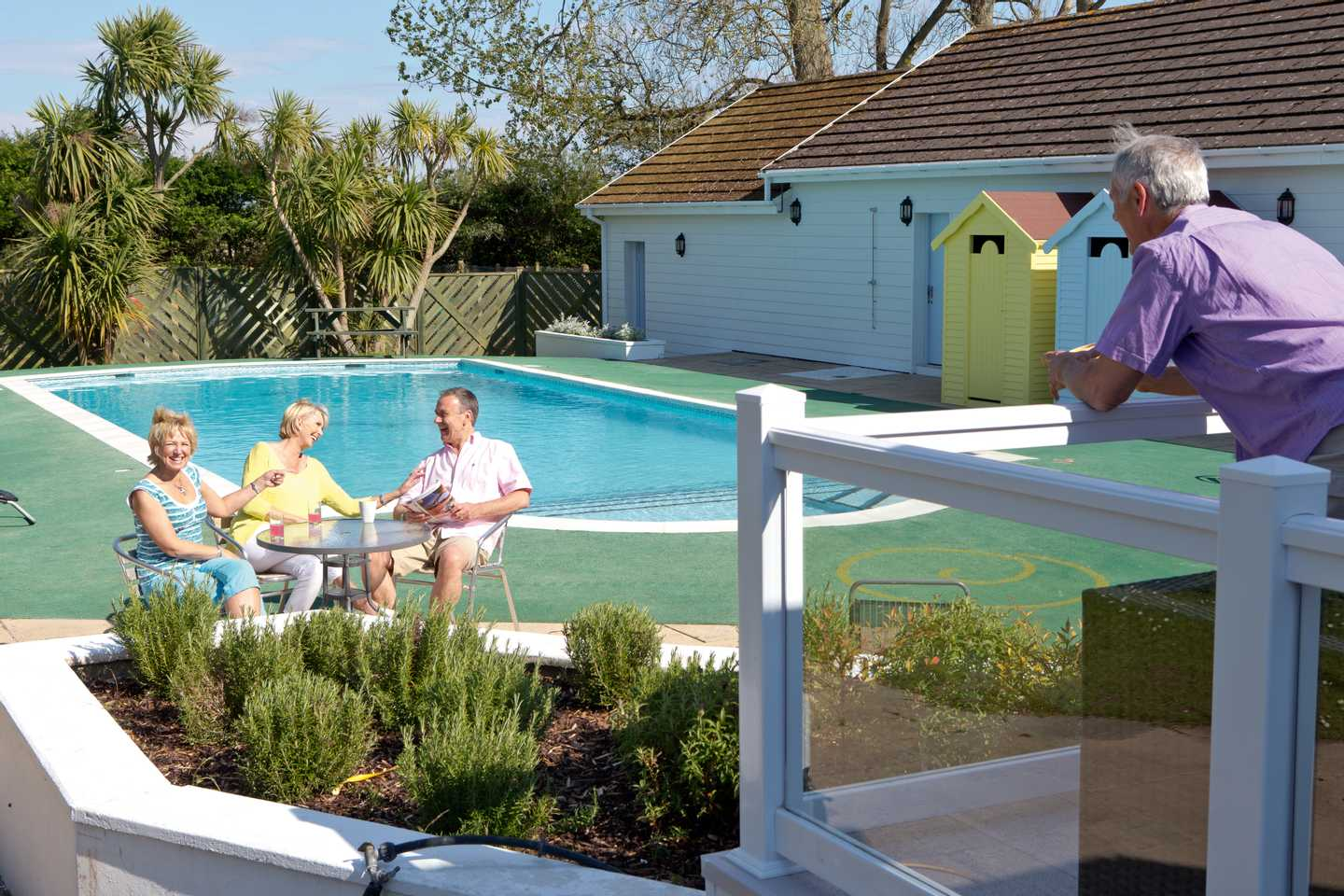 Guests having a drink by the heated outdoor pool
