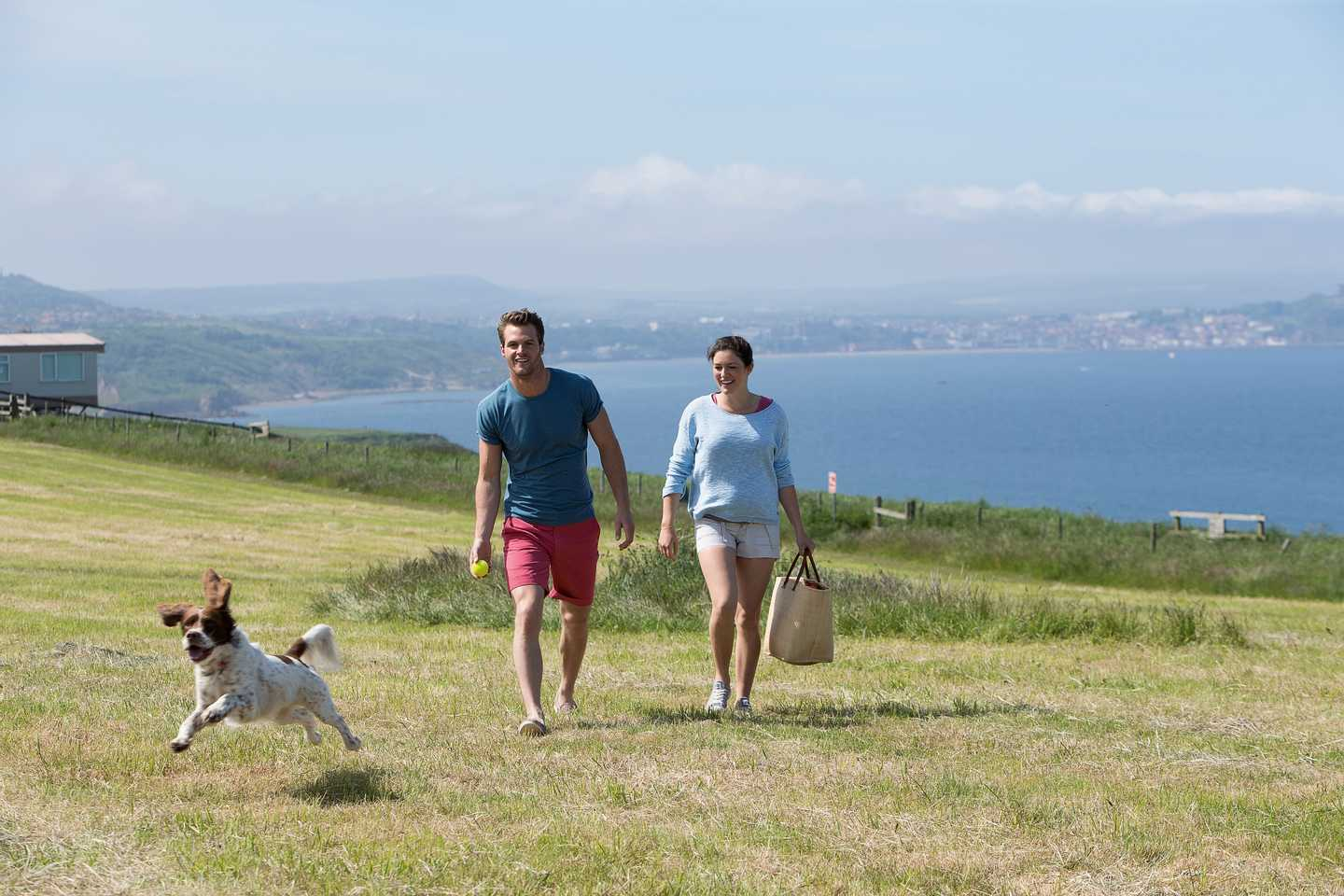 A couple walking their dog on the grass overlooking the sea