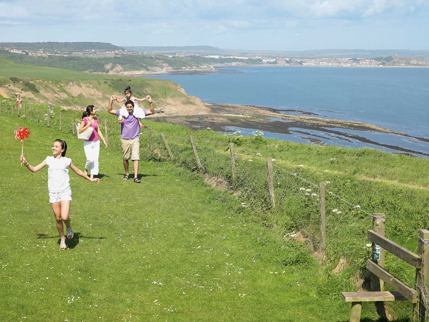 Family walking along the clifftops overlooking the sea