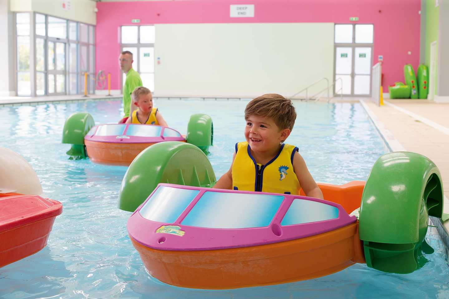 Child navigating the indoor pool in an Aqua Paddler