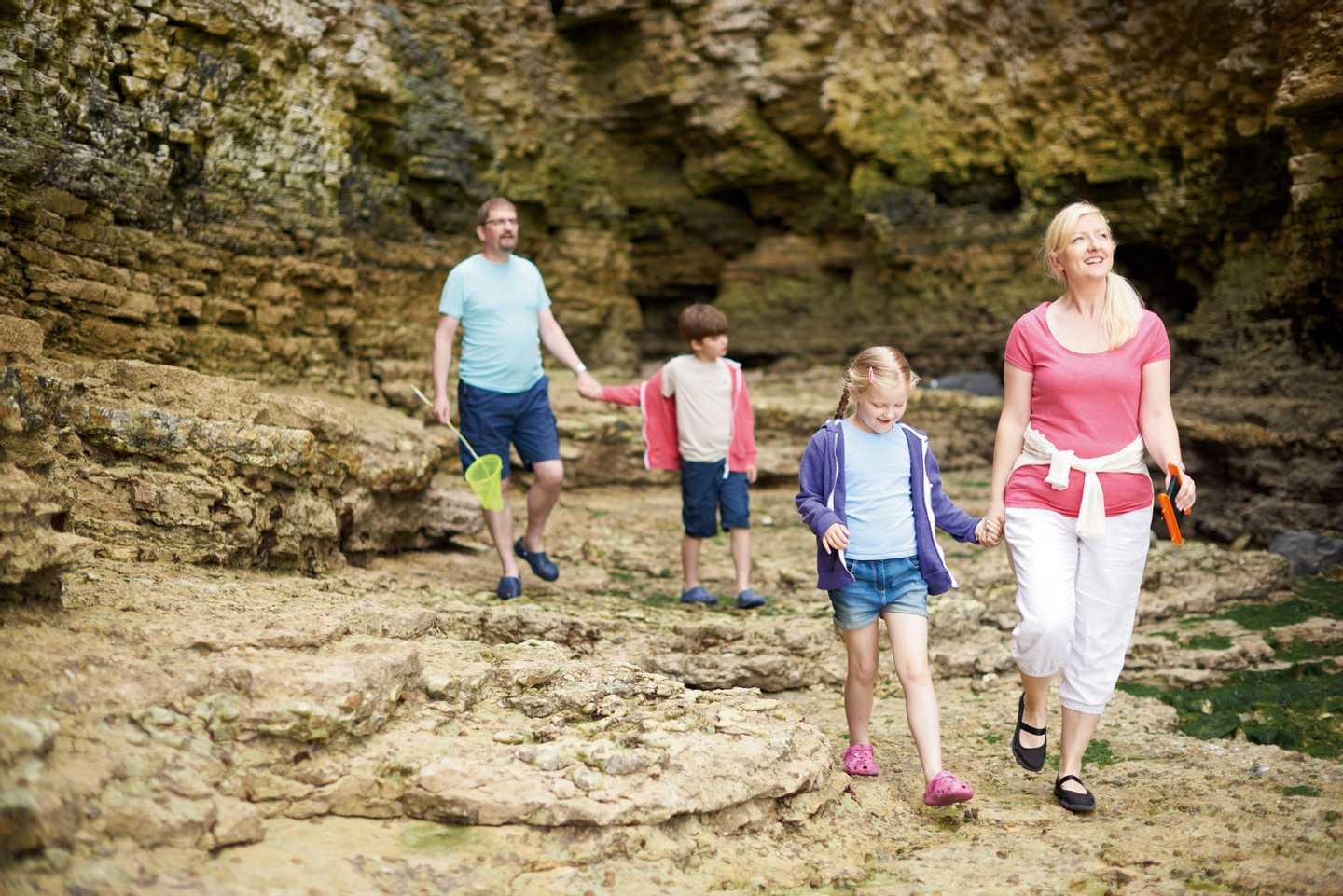 A family walking along the beach at Thornwick Bay