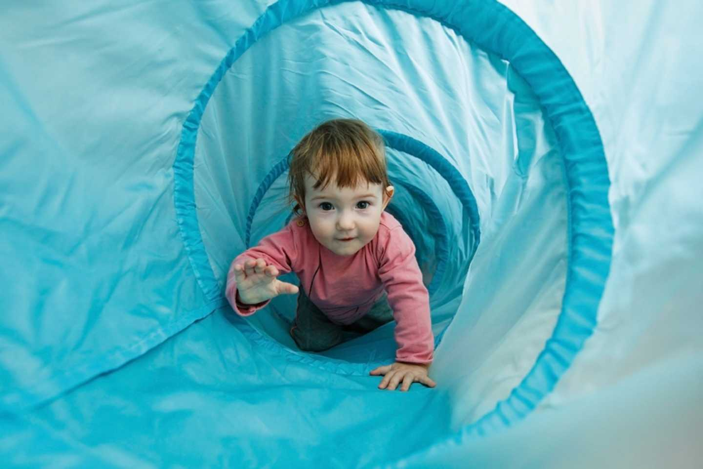 Toddlers exploring a coloured play tunnel