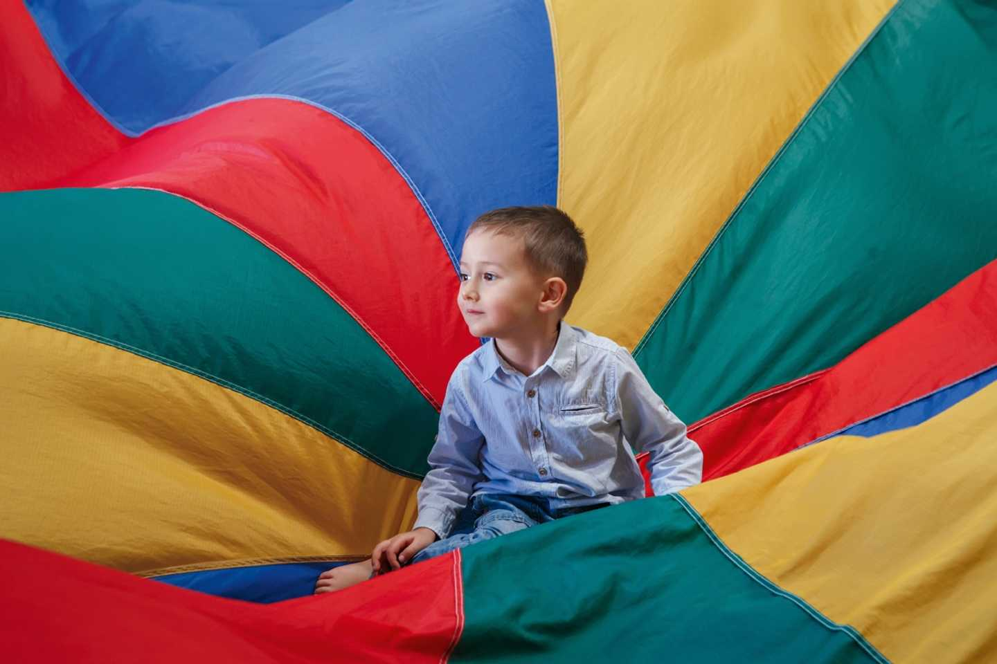 Toddler playing in parachute game