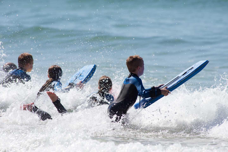 Children surfing at the beach