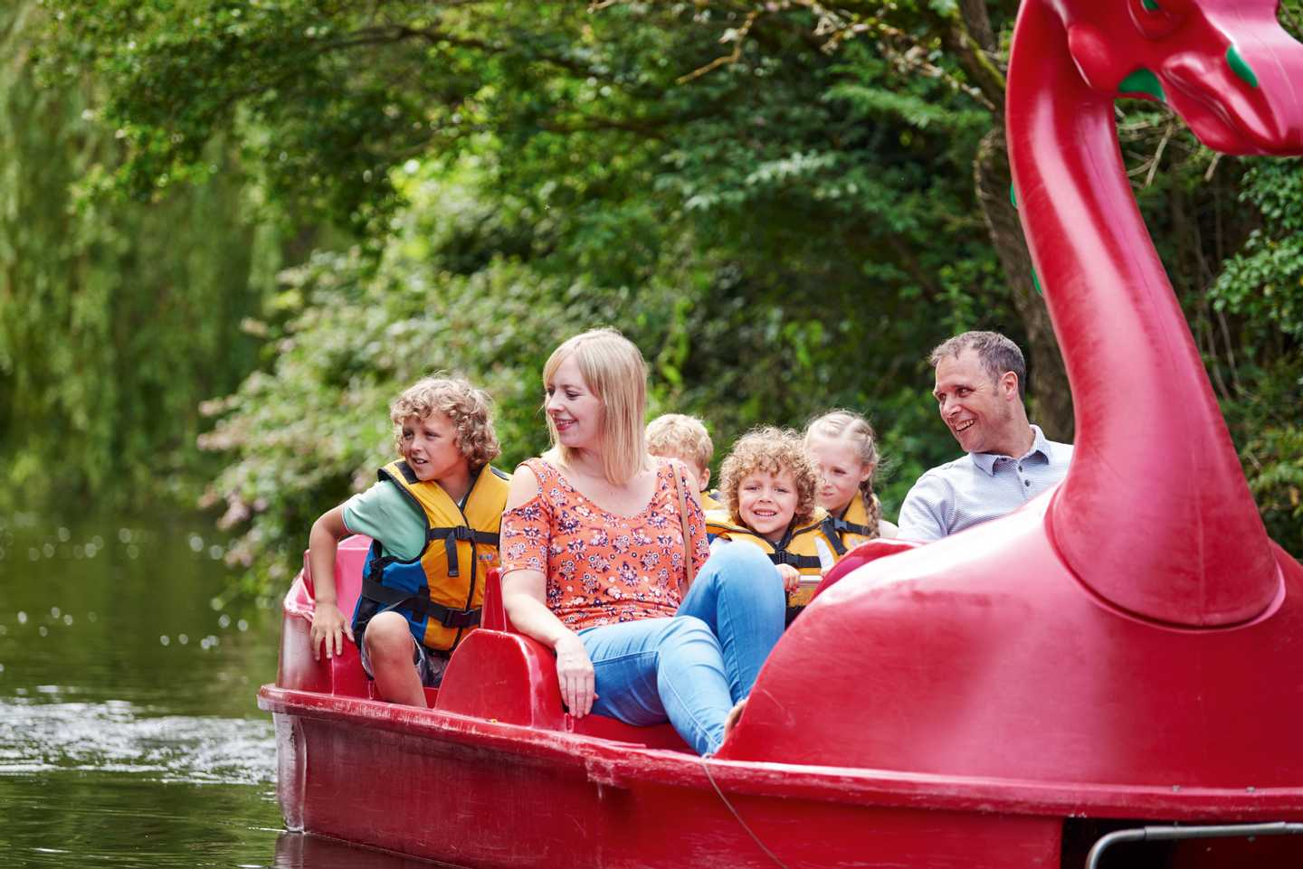 Family sailing around the boating lake on a giant swan