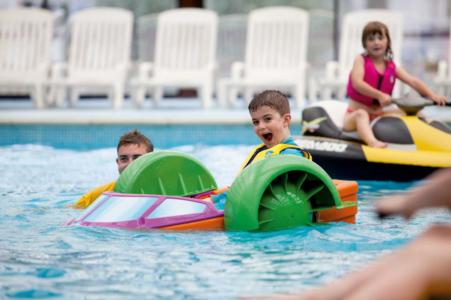 Child navigating the pool in a Aqua Paddler