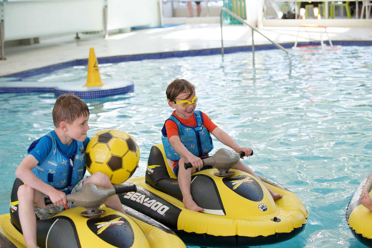 Children navigating the pool on Aqua Gliders