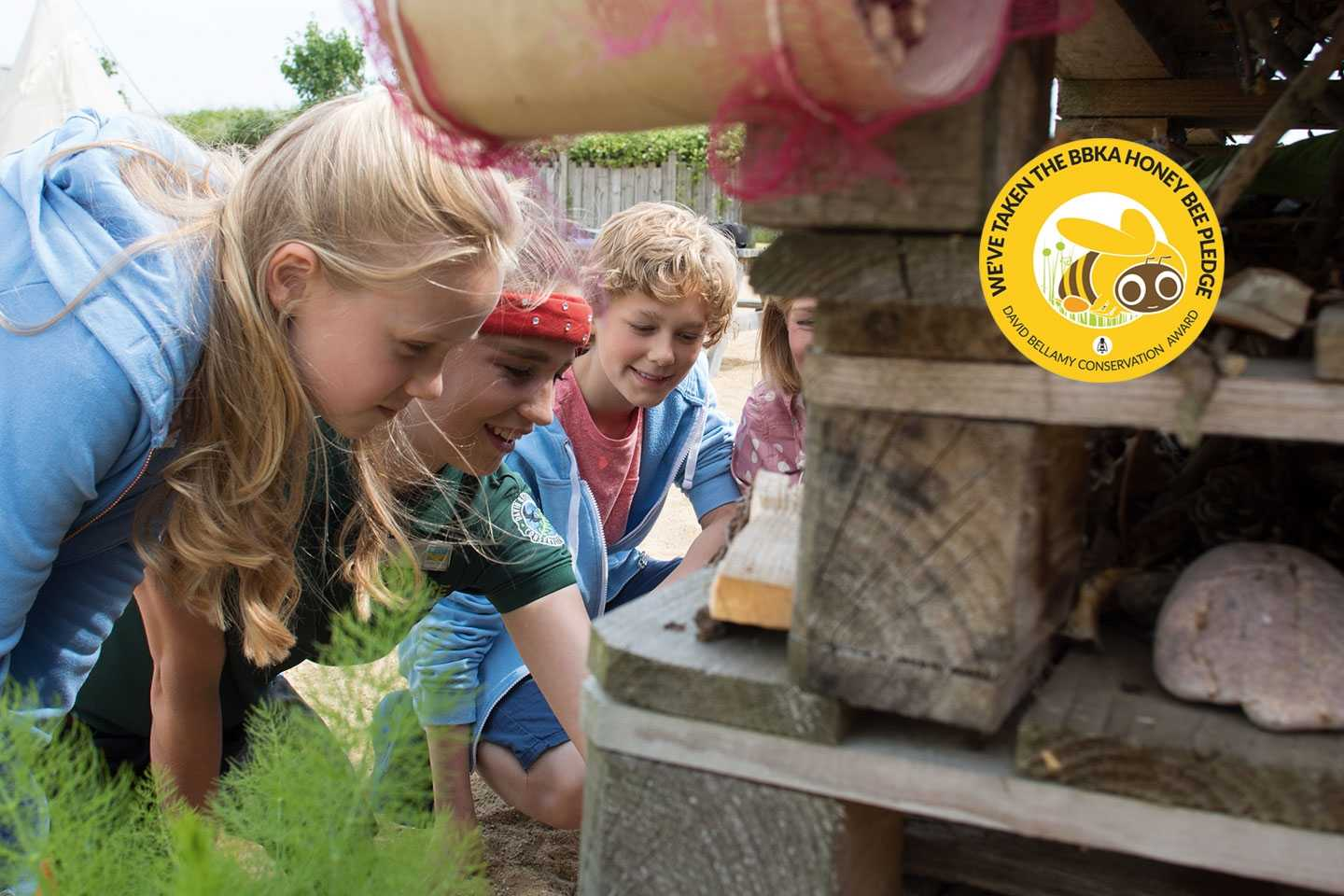 Bug hotel with the Honey Bee Pledge logo