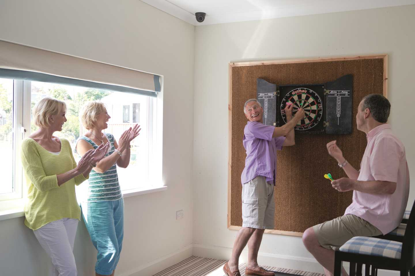 A group of friends having a game of darts in our Owners' Lounge