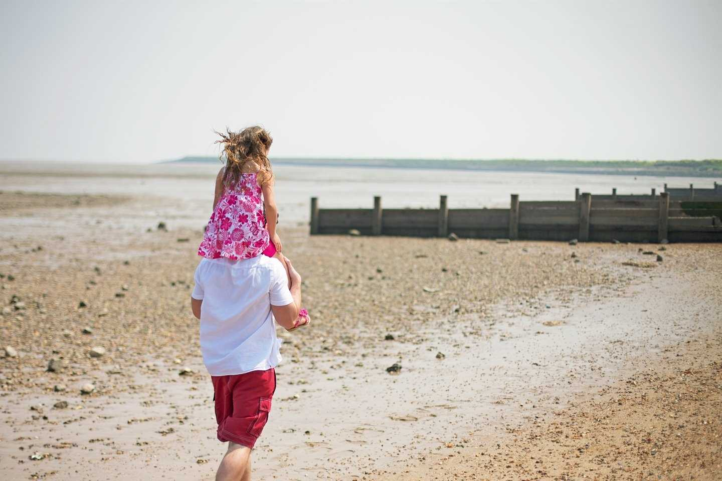 Girl on her father's shoulders walking along the beach
