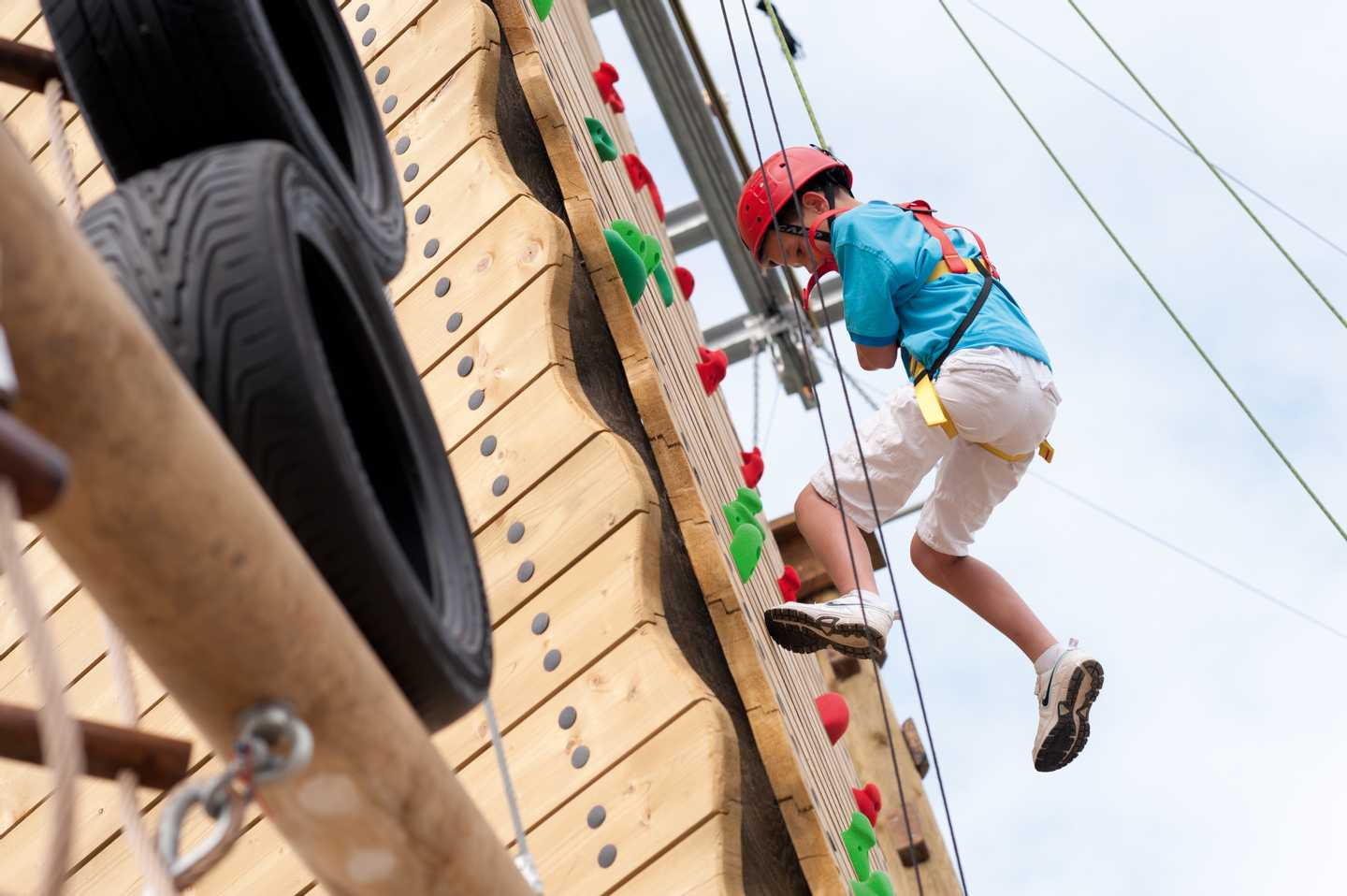 A young boy climbing the climbing wall