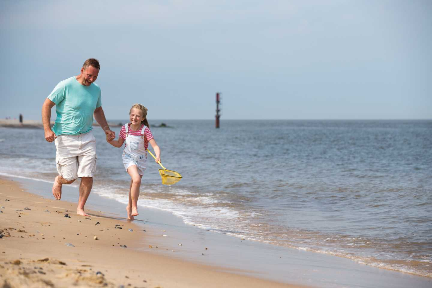 Father and daughter running along the shoreline