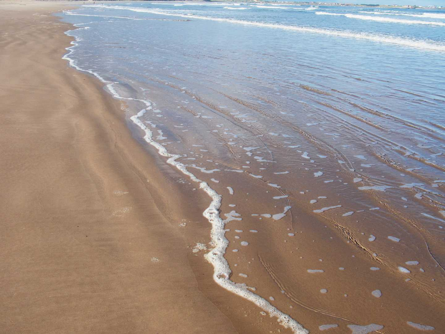 Waves washing over sand