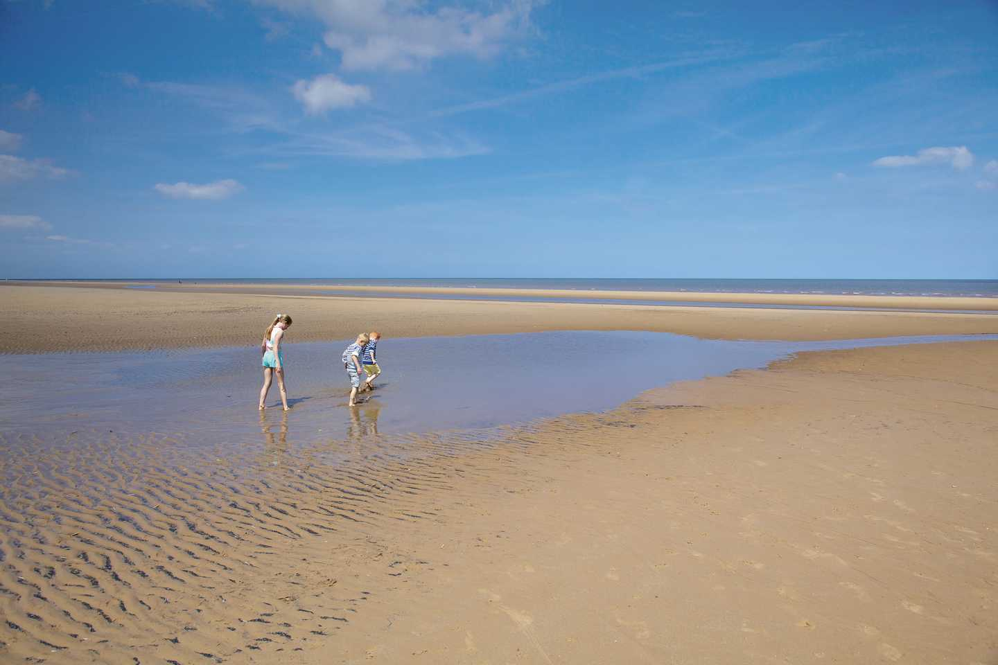 Children walking along the sand