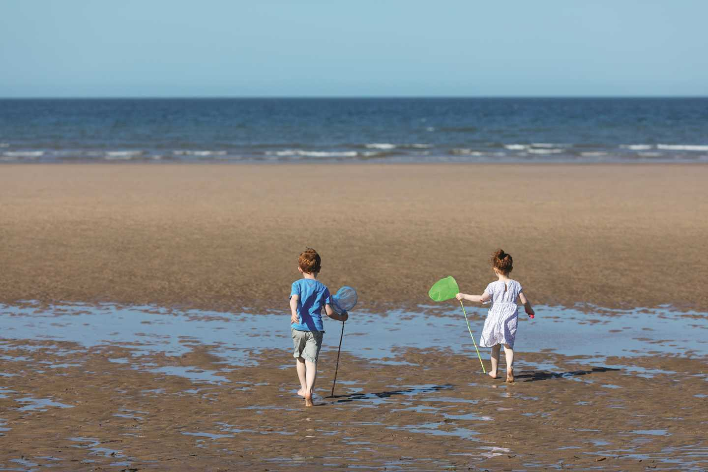Boy and girl with fishing nets at the beach