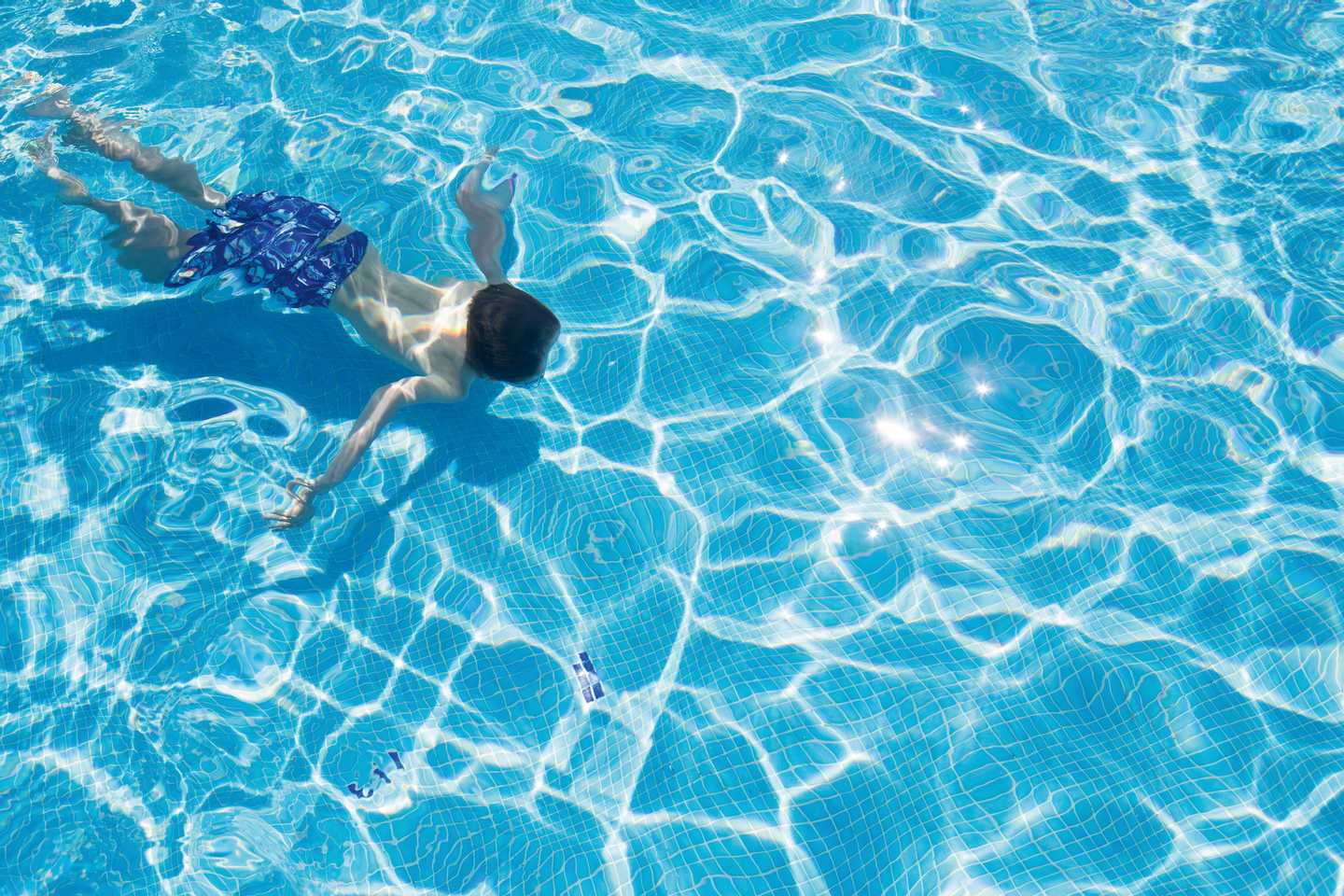 Boy swimming under water in the outdoor swimming pool at Combe Haven