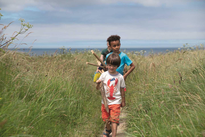 Children walking through long grass