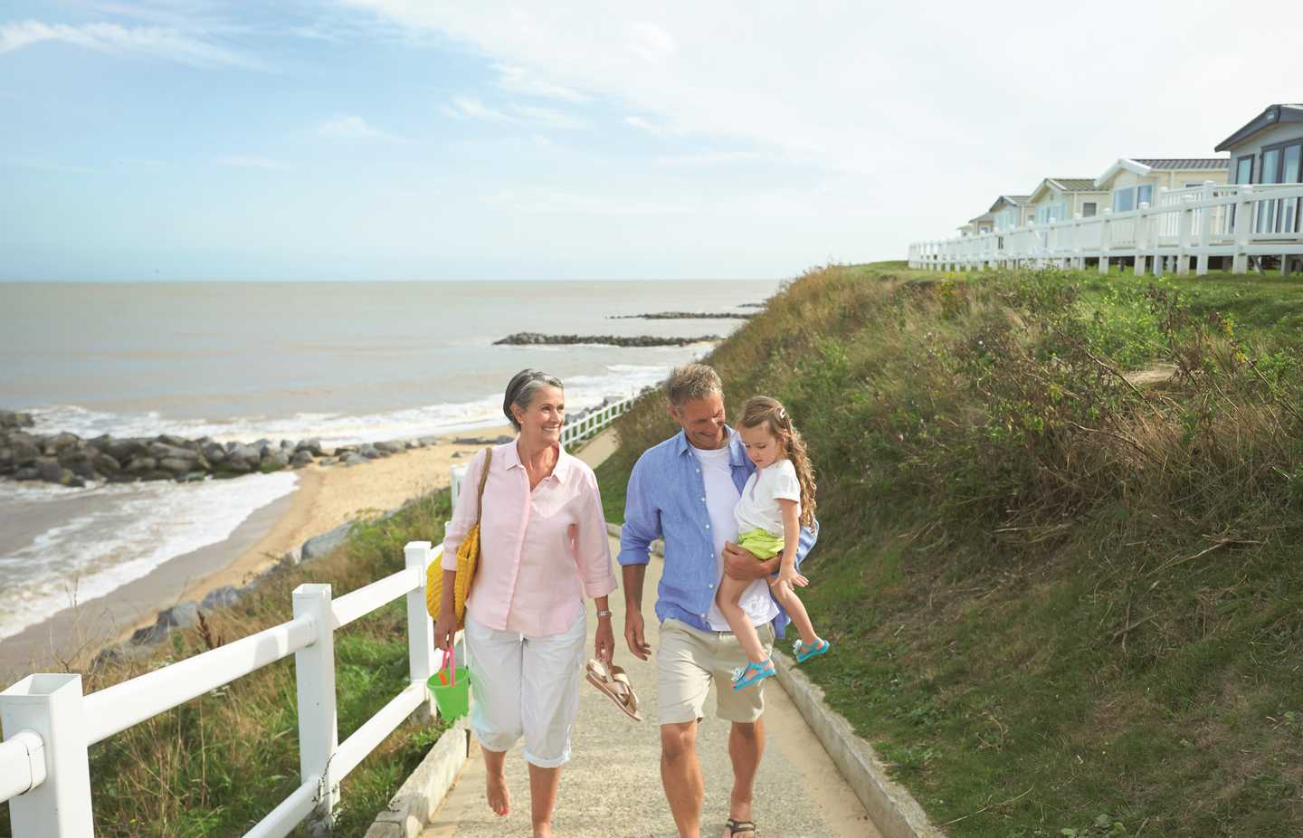 A family walking up the path from the beach