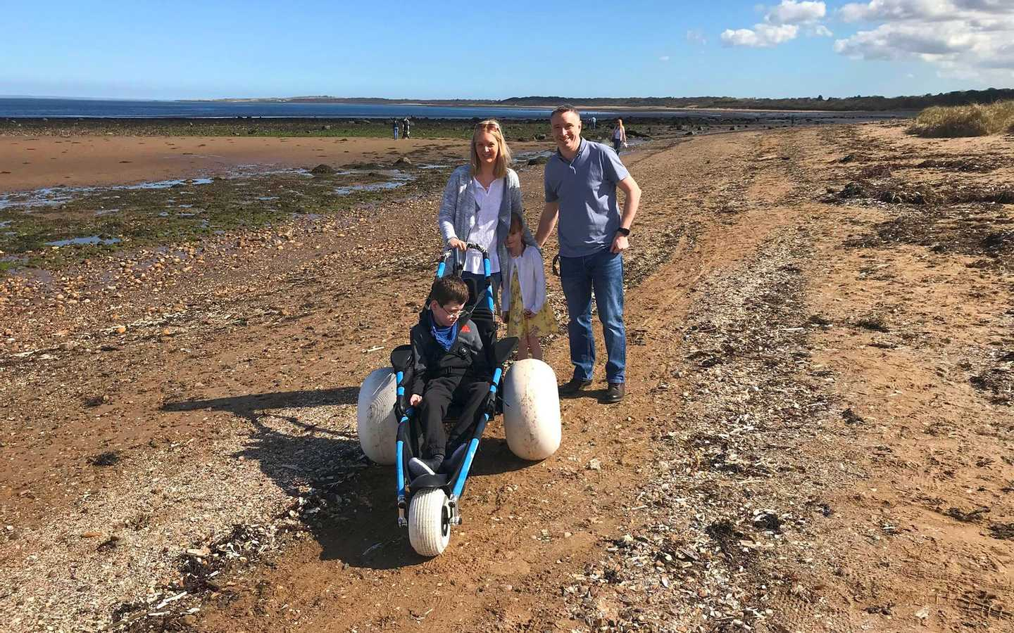 A family with a beach wheelchair