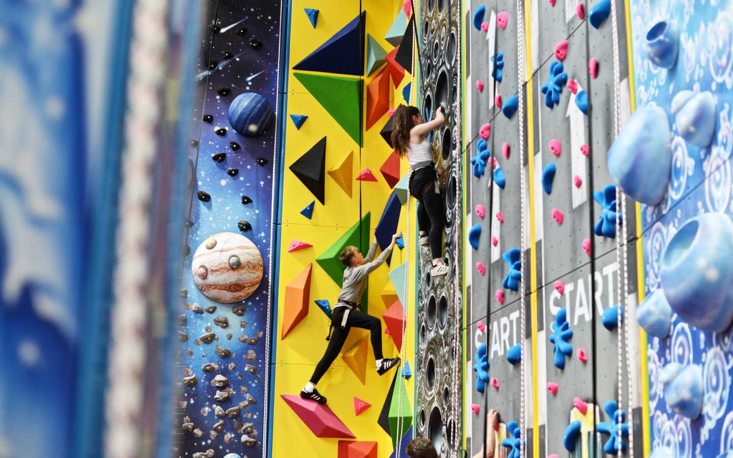 Children making their way up the climbing wall