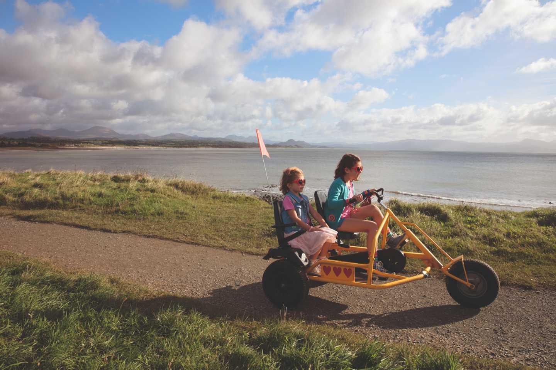 Children riding a kart by the beach