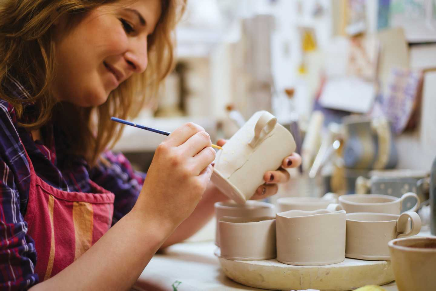 Lady lovingly painting her pottery creation