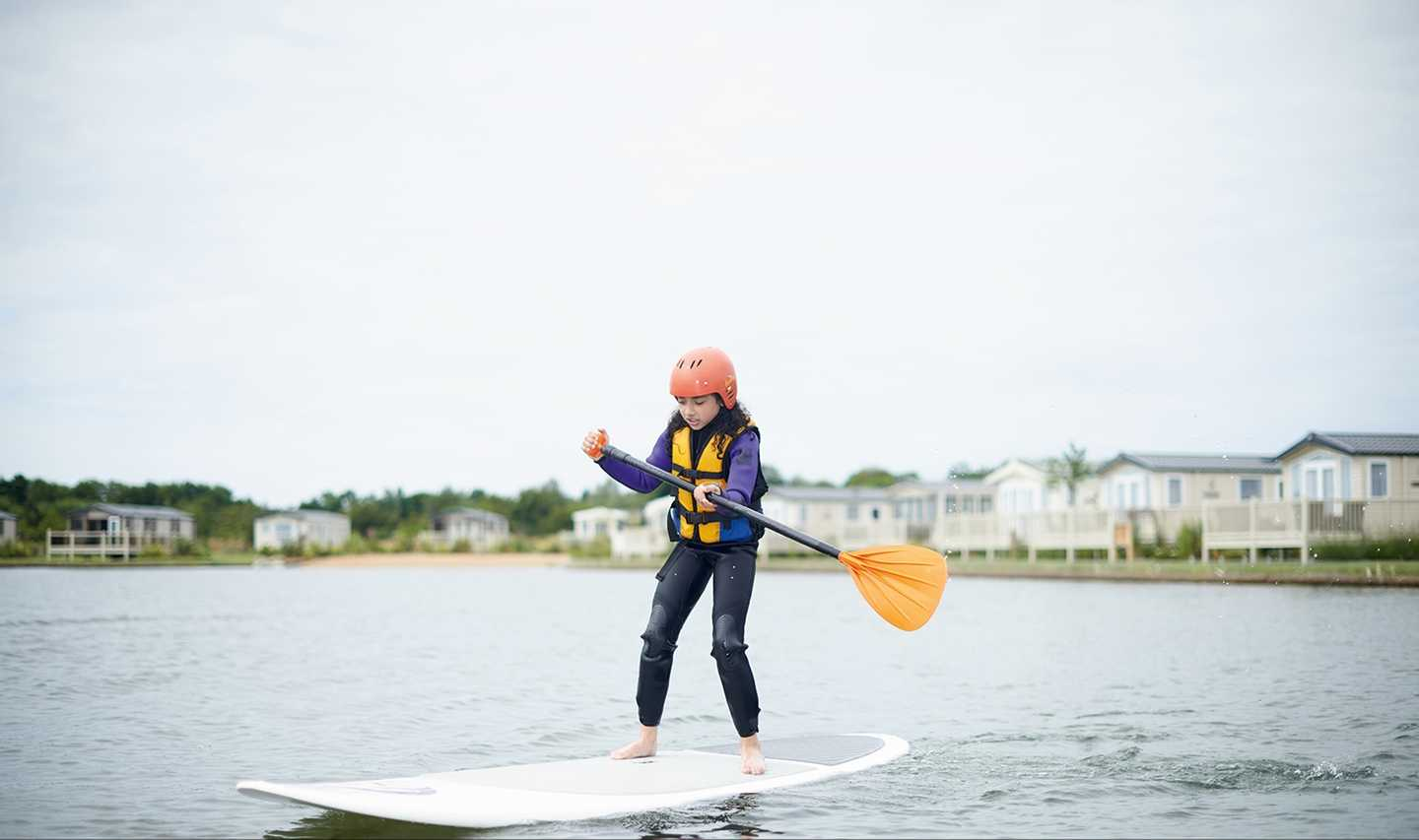 Child in wetsuit enjoying lake paddleboarding