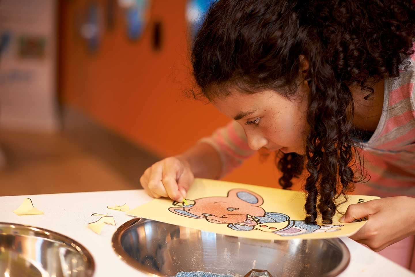 A young girl doing sand art