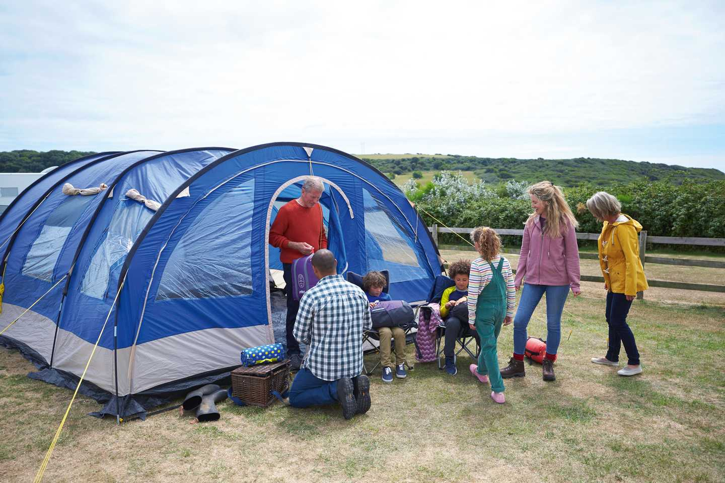 A family sitting beside their tent at Littlesea