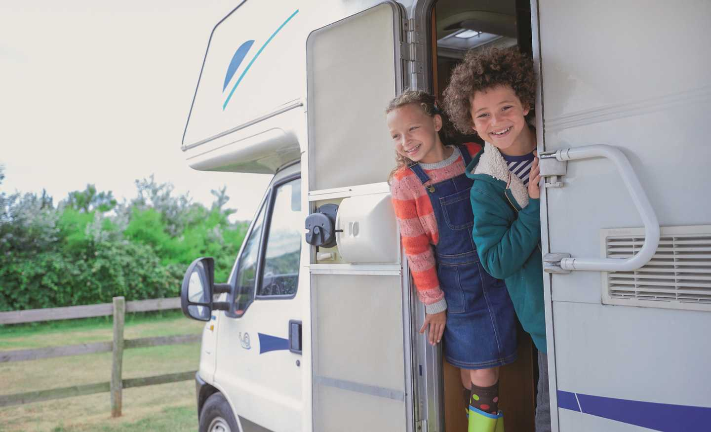 Children peering out the door of their motorhome