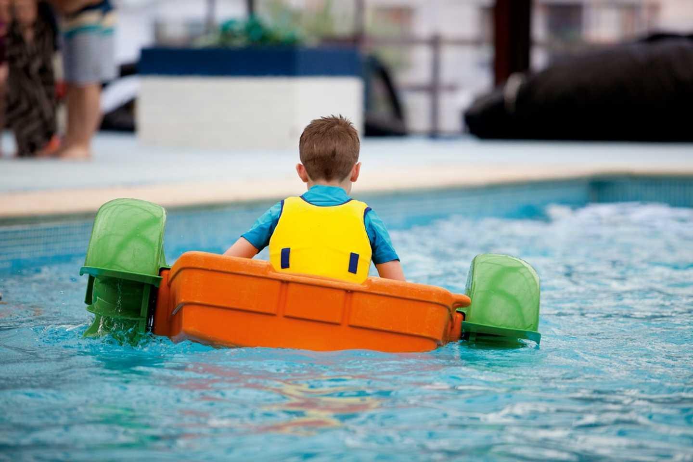 Boy playing in pool on Aqua Paddlers