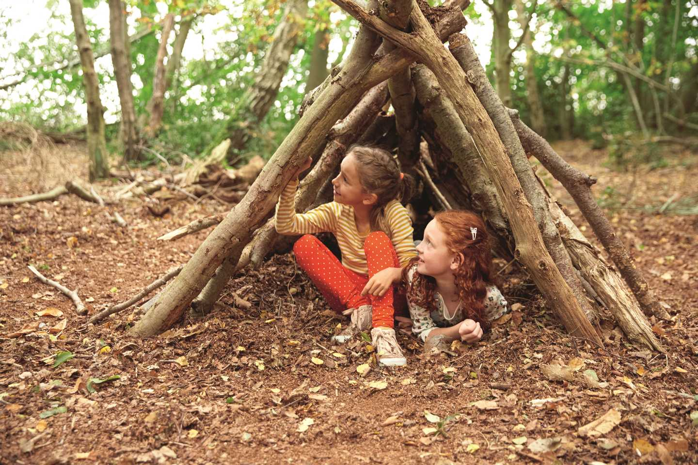 2 children building a den in the woods