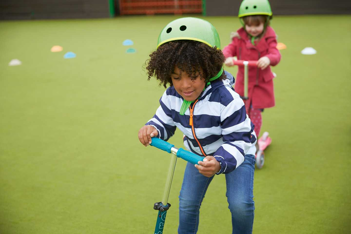 Children playing on mini scooters in the sports court