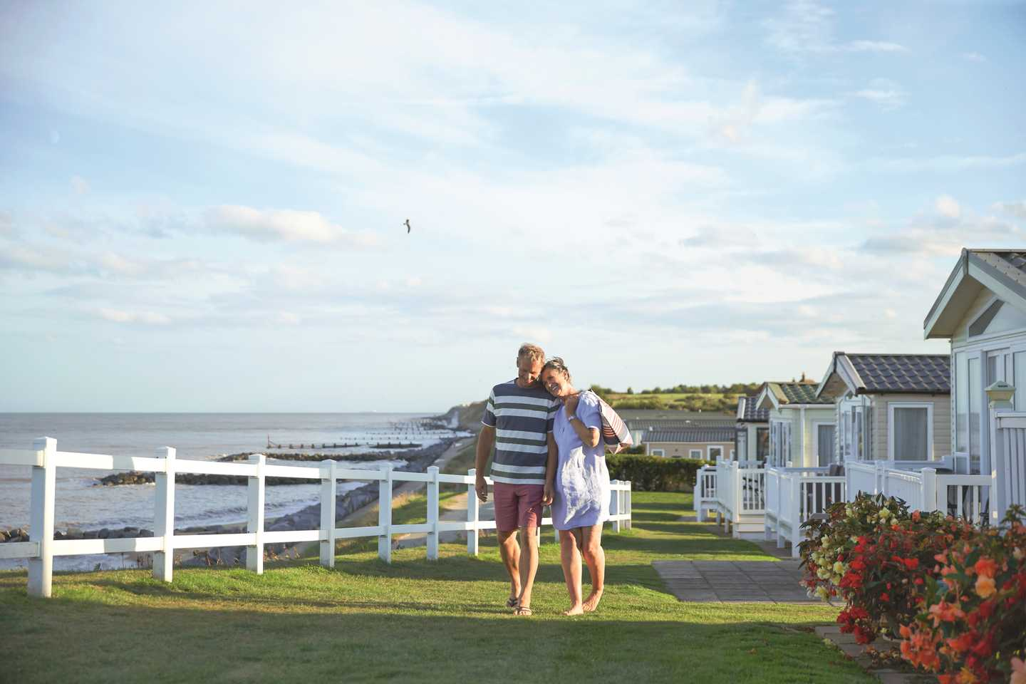 A couple beside a holiday home at Hopton