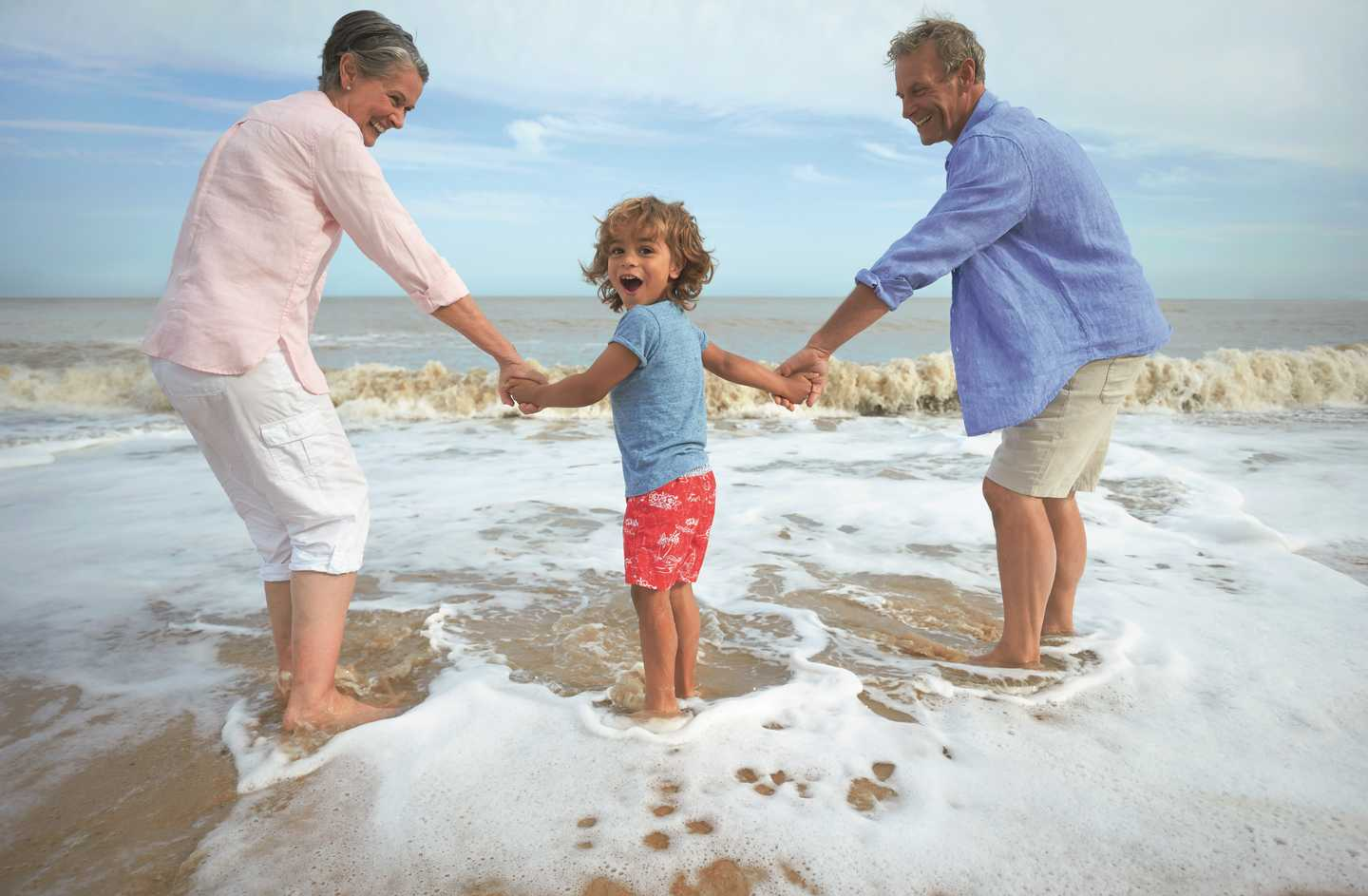 A child and his grandparents walking into the sea at Hopton